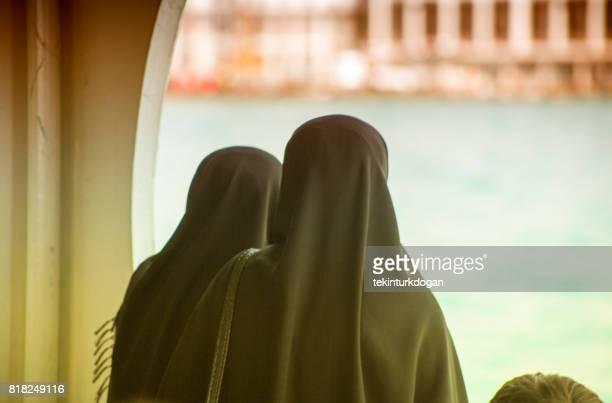 religiöse frauen mit schwarzen burka am fahrgastschiff in der bosporus-istanbul-türkei - burka stock-fotos und bilder
