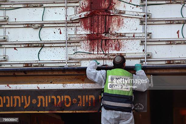 Religous Jew from the ZAKA volunteer organization collects body parts at the blood-stained scene of a Palestinian suicide bombing February 4, 2008 in...