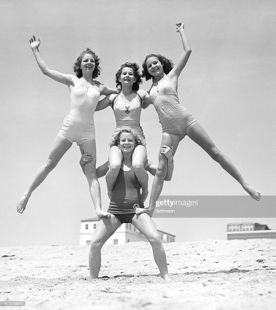 Woman Supporting Three Balancing Girls : News Photo