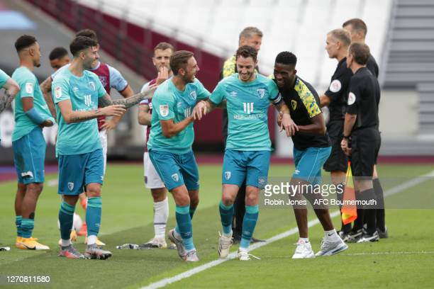 Reluctant captain Adam Smith of Bournemouth is encouraged by teammates Diego Rico, Dan Gosling and Jefferson Lerma to receive Betway Cup after the...