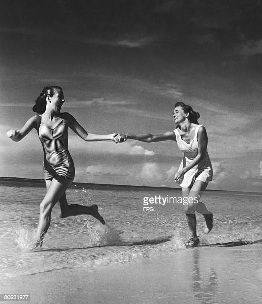 A reluctant runner is pulled along the beach by her more enthusiastic friend circa 1940