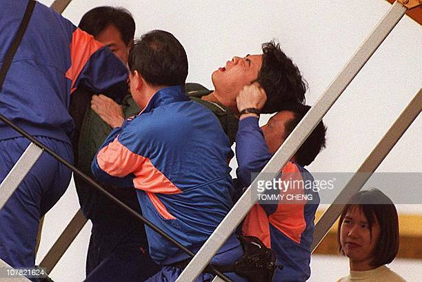 A reluctant Vietnamese returnee shown in file photo dated 08 March 1995 as he is pushed into a plane by the Hong Kong authorities under the Orderly...