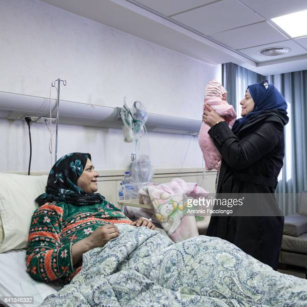 Remah Bauod with her sister and her daughter Racha born a few hours before in a room at 'u201cRazan'u201d fertility clinic in Nablus'nHer husband...