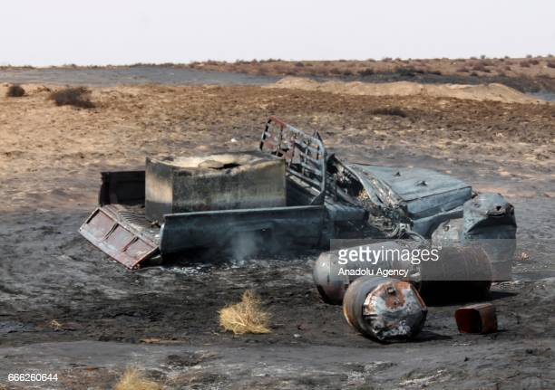 Remains of a burnt car and oil barrels are seen at the explosion site in Al Hudaydah Yemen on April 8 2017 Yesterday unidentified attackers started a...