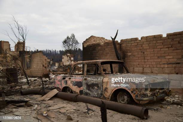 Remains of a car outside a burned house in the frontline village of Metolkyne outside Luhansk on October 3, 2020 in Luhansk, Ukraine. Shelling from...