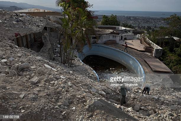 Remains of a hotel that collapsed during the earthquake February, 2011 in Port-au-Prince, Haiti. Men look for scrap metal in the remains as a source...