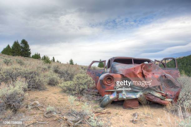 remains of a wrecked car in a field - horrible car accidents stock pictures, royalty-free photos & images