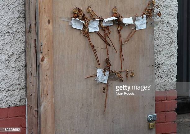 Remains of floral tributes on the front door are seen as builders begin to demolish the semidetached house at 18 Victory Road where six children died...