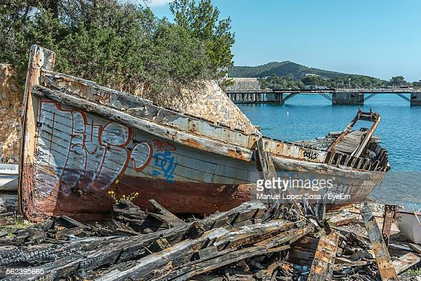 Remains Of Old Wooden Broken Ruined Boat Abandoned On Coastal Land