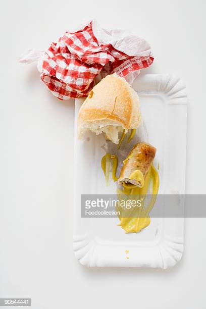 Remains of sausage with mustard and bread roll on paper plate