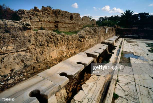 Remains of the limestone latrines inside the Hadrianic Baths part of the ruins of Leptis Magna the largest city of the ancient region of Tripolitania...