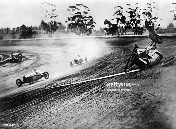 Remarquable instantané pris pendant une course de bolides où le pilote dérape dans le virage sa voiture fait plusieurs tonneaux et s'arrête...