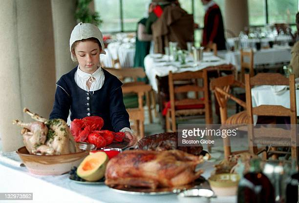 Remember Allarton played by Hila Bernstein sets a table with the Thanksgiving feast served at Plimoth Plantation in Plymouth Mass