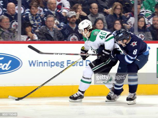 Remi Elie of the Dallas Stars plays the puck along the boards as Jacob Trouba of the Winnipeg Jets gives chase during first period action at the Bell...