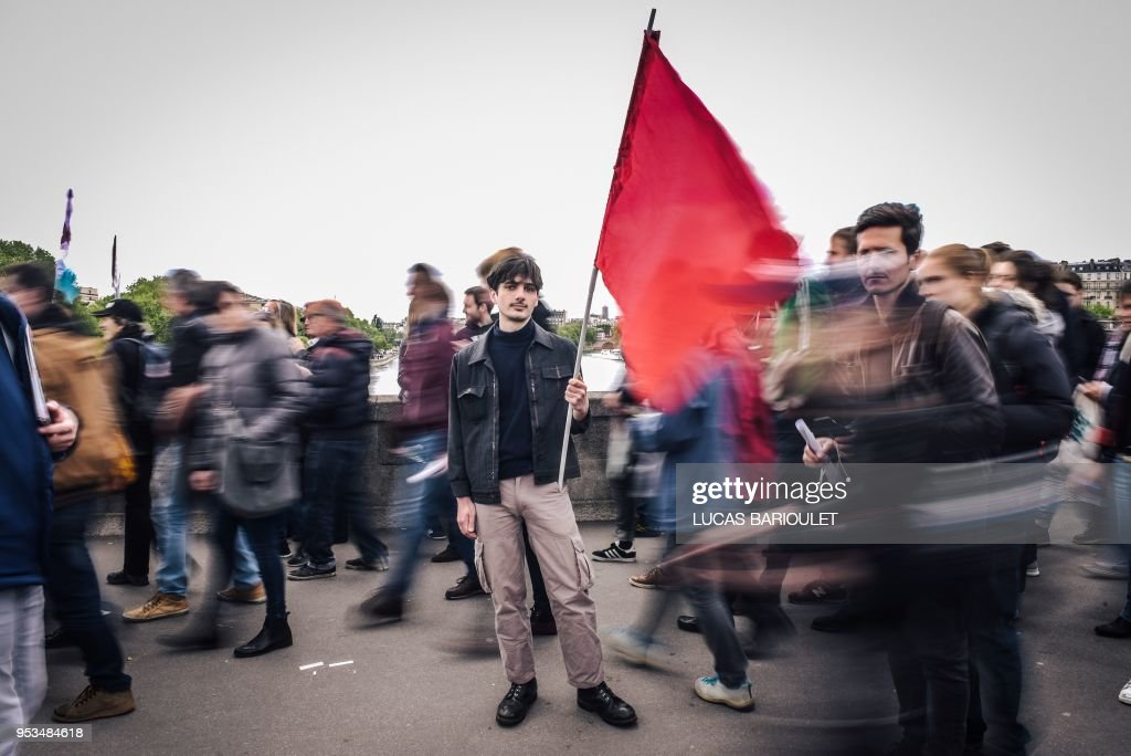 TOPSHOT - Remi Faussemagne, a 22 year old, student and cashier, poses during the annual May Day workers' rally in Paris on May 1, 2018.