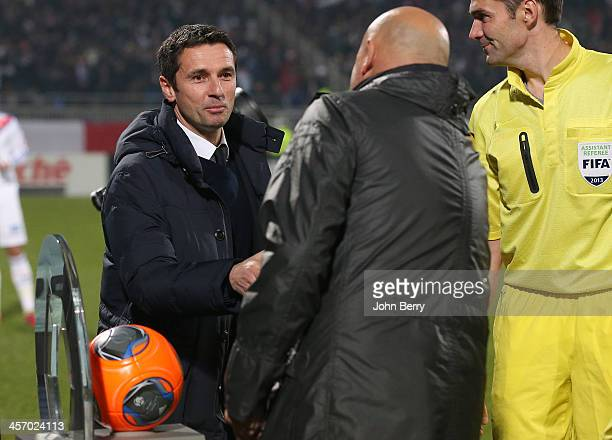 Remi Garde coach of Lyon shakes hands with Jose Anigo new coach of Marseille prior to the french Ligue 1 match between Olympique Lyonnais OL and...