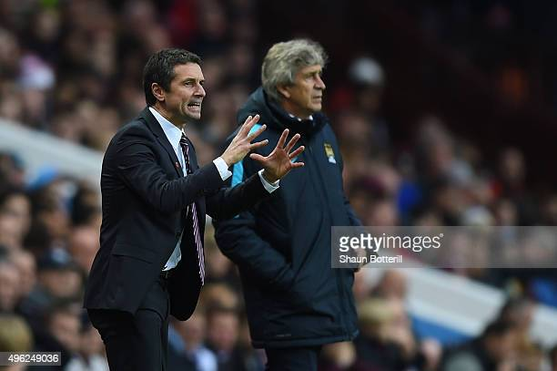 Remi Garde Manager of Aston Villa directs his players as Manuel Pellegrini the manager of Manchester City looks on during the Barclays Premier League...