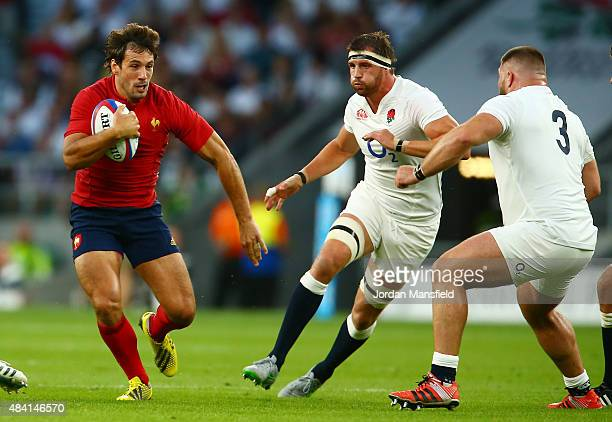 Remi Lamerat of France goes past Tom Wood of England during the QBE International match between England and France at Twickenham Stadium on August 15...