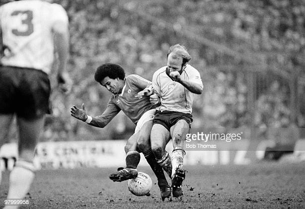 Remi Moses of Manchester United clashes with Derby County captain Archie Gemmill during the FA Cup 5th Round match held at The Baseball Ground Derby...