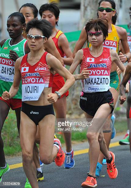 Remi Nakazato of Japan and compatriot Azusa Nojiri compete in the Women's Marathon of The World Athletics Championships in Daegu on August 27 2011...