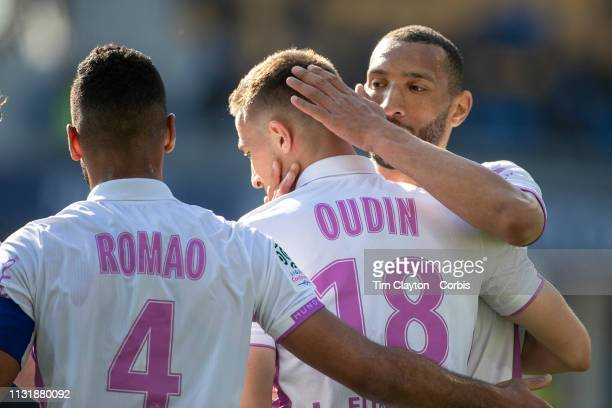 Remi Oudin of Stade de Reims is congratulated after scoring the first of his two goals by Yunis Abdelhamid of Stade de Reims and Alaixys Romao of...