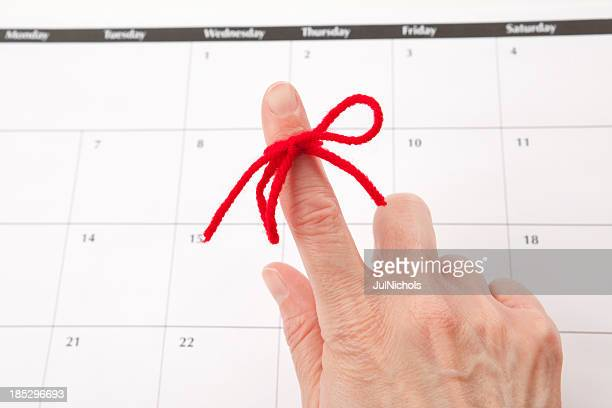 reminder: red ribbon on finger with calendar - string stock pictures, royalty-free photos & images