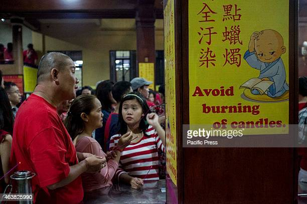 Reminders about burning of candles are posted on the walls of Seng Guan temple to guide the shrine goers