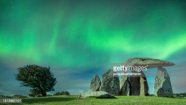 remnants of a neolithic burial chamber, in the evening with beautiful green northern lights. imagine the druids - rock stock pictures, royalty-free photos & images