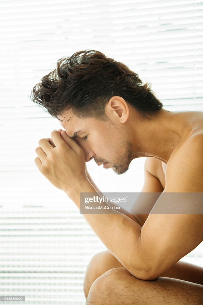 Remorseful man deep in thoughts vertical version : Stock Photo