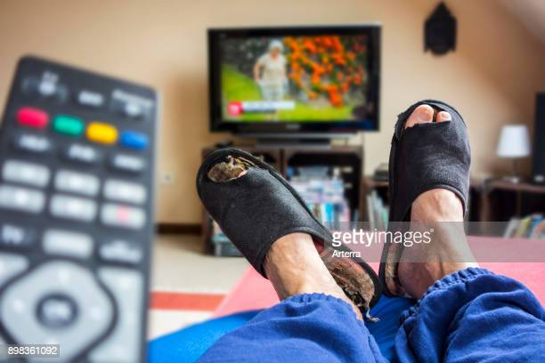 Remote control and couch potato lazy man in comfy chair wearing worn slippers with big toes sticking through and watching television in living room