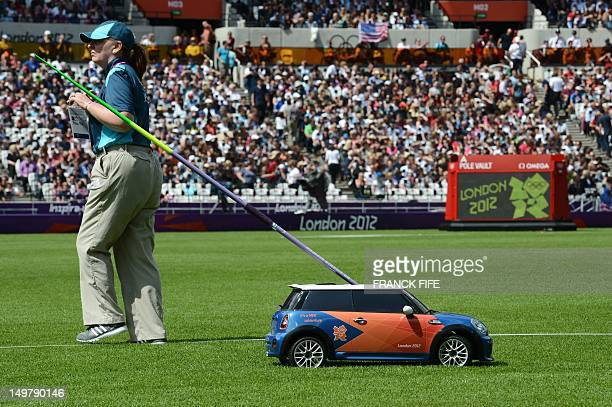 A remote control car brings back a javelin during the women's heptathlon javelin throw qualifications at the athletics event of the London 2012...