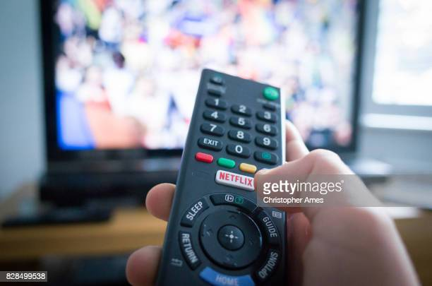 tv remote control with netflix button - television industry stock photos and pictures
