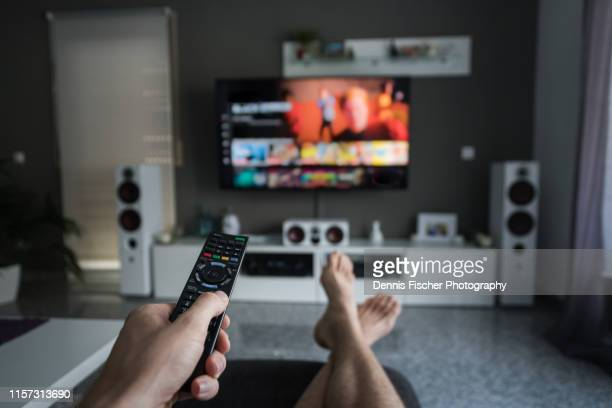 remote control with television in living room - arts culture and entertainment stock pictures, royalty-free photos & images