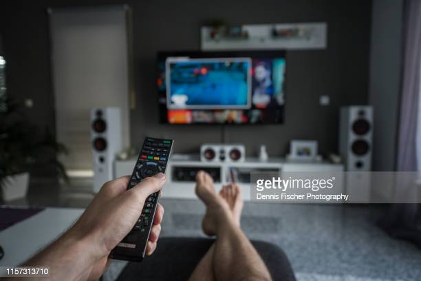 remote control with television in living room - entertainment center stock pictures, royalty-free photos & images