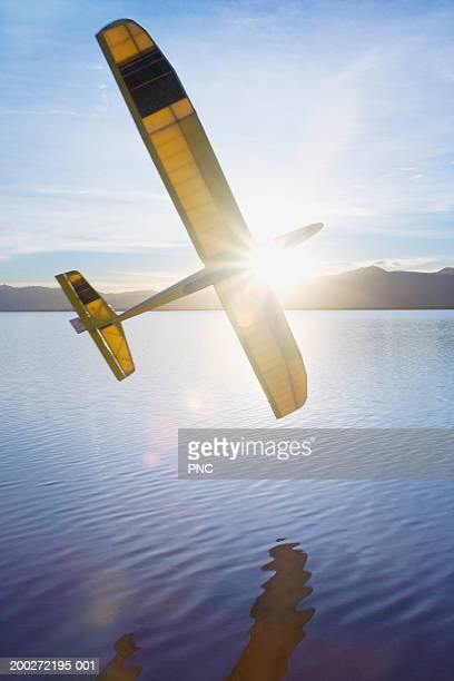 Remote controlled glider flying in sunlight over lake