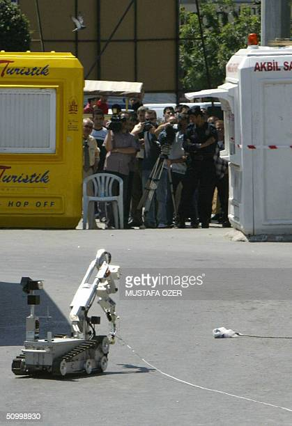 A remote controlled robot approaches to set a detonator on a suspicious package which was found on a bus in Taksim Square as officials evecuate the...