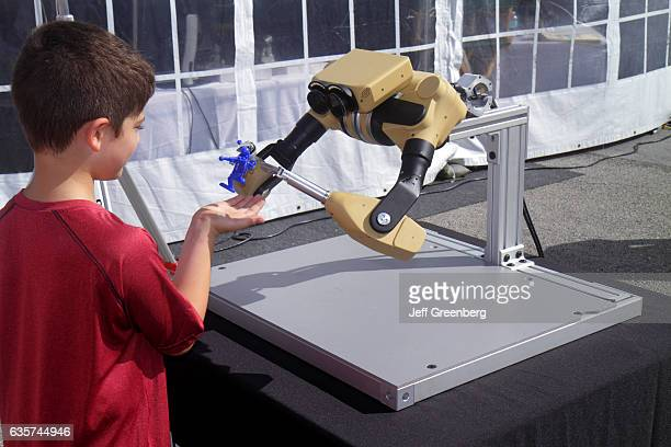 A remote controlled robot arms picking up a toy from a boy at the DARPA Robotics Challenge Trials