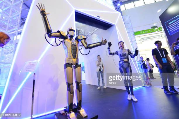 Remote controlled robot copies the movement of a woman wearing sensor suit on day two of China International Big Data Industry Expo 2019 at Guiyang...