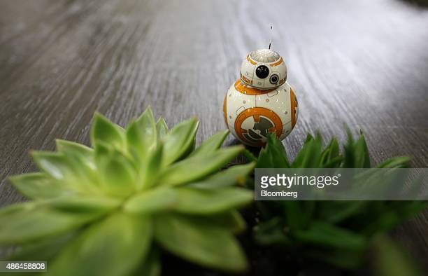 A BB8 remote controlled robot toy from the forthcoming Walt Disney Co Star Wars movie franchise sequel moves around an exhibition display during the...