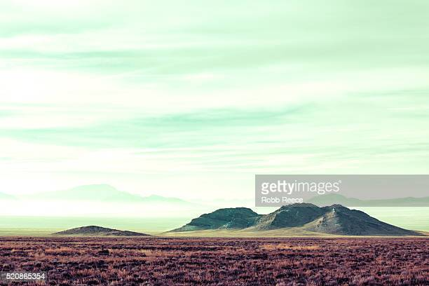 a remote, desolate, desert landscape with mountains in the background. - robb reece stockfoto's en -beelden