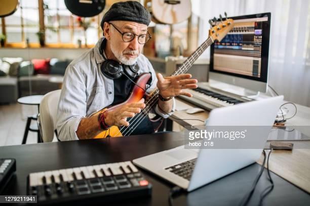 onderwijs op afstand - muzieklessen - alleen seniore mannen stockfoto's en -beelden