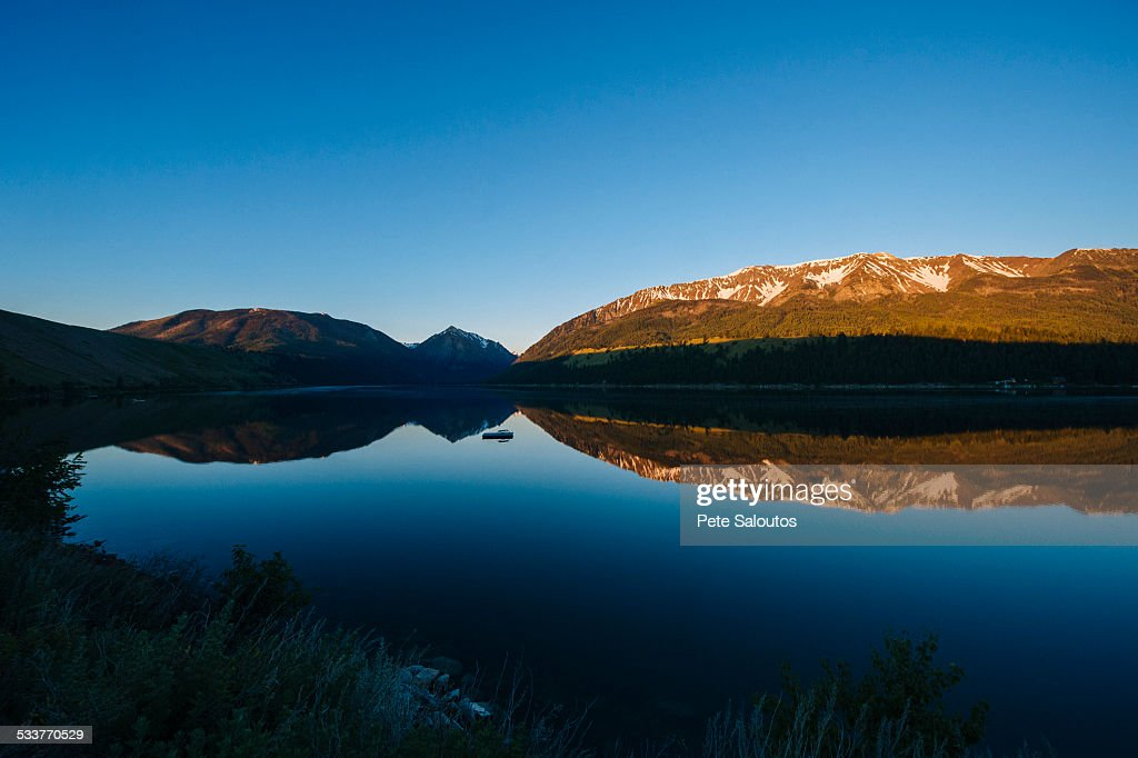 Remote mountains and blue sky reflected in still lake : Foto stock