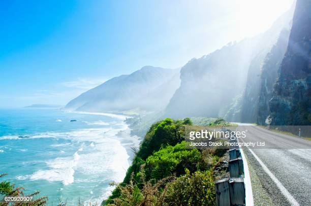 remote road on scenic coastal cliff - new zealand stock pictures, royalty-free photos & images