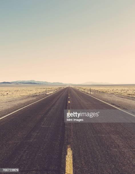 Remote rural road through a flat arid landscape to the horizon.