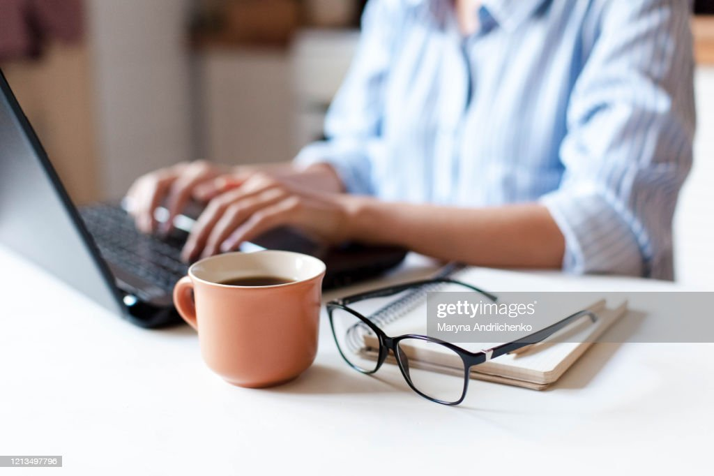 Remote working from home. Freelancer workplace in kitchen with laptop, cup of coffee : Stock Photo
