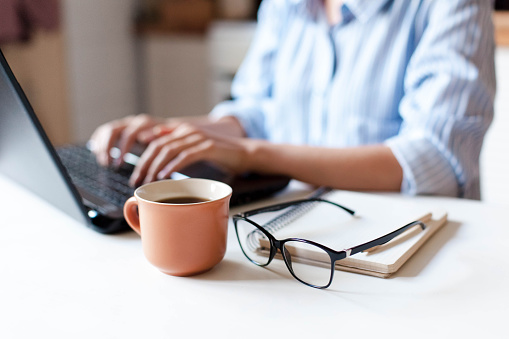 Remote working from home. Freelancer workplace in kitchen with laptop, cup of coffee 1213497796