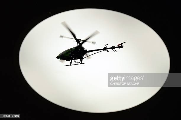 A remotecontrolled helicopter flys in front of a light at a booth during the press preview of the international toy fair in Nuremberg southern...