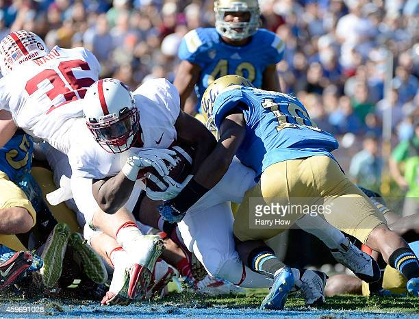 Remound Wright of the Stanford Cardinal runs in for a touchdown as he is hit by Fabian Moreau of the UCLA Bruins during the first quarter at Rose...