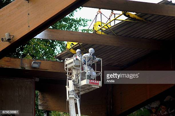 Removal of asbestos on the former football stadium GrimonprezJooris in Lille Two workers wearing overalls and a mak here in a cradle on the...