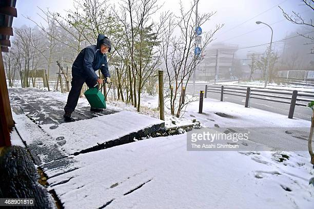 A removes snow from a deck of the Rokkosan Guide House at Mount Rokko on April 8 2015 in Kobe Hyogo Japan A coldair system covers eastern and central...